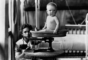 A Nurse Weighs a Baby on a Basket Scale, 1912